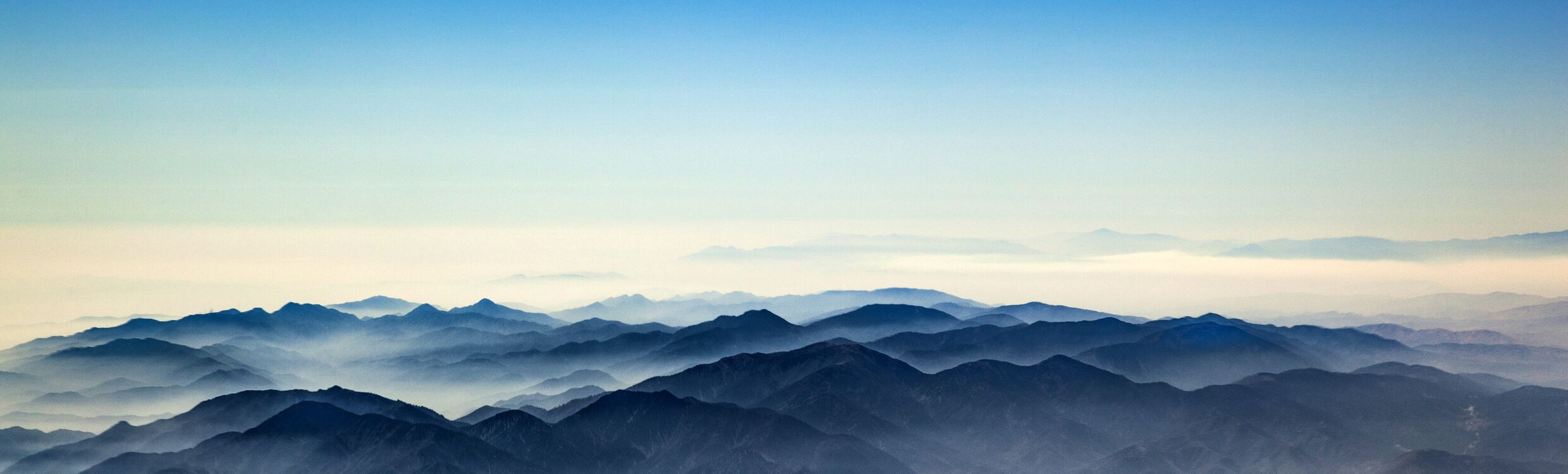 Photo of distant mountains in mist and pale blue sky